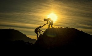 An image of mountain climbers helping each other.